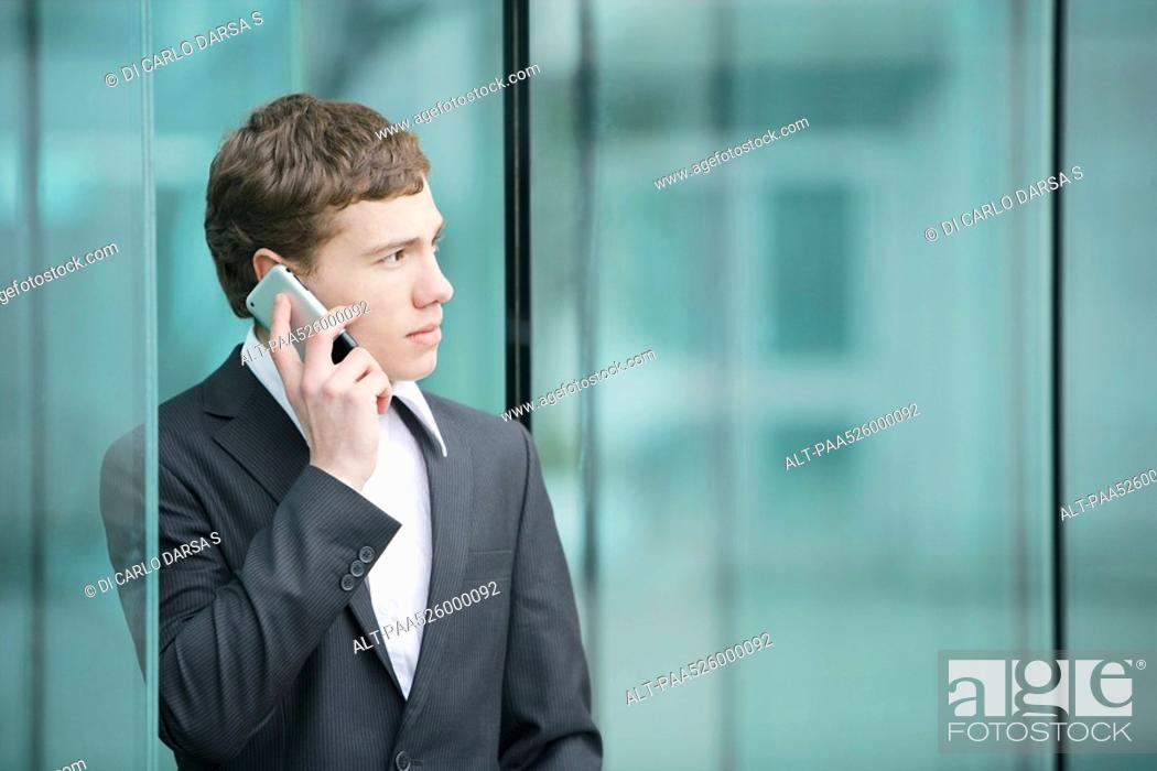 Stock Photo: Businessman using cell phone, looking away.