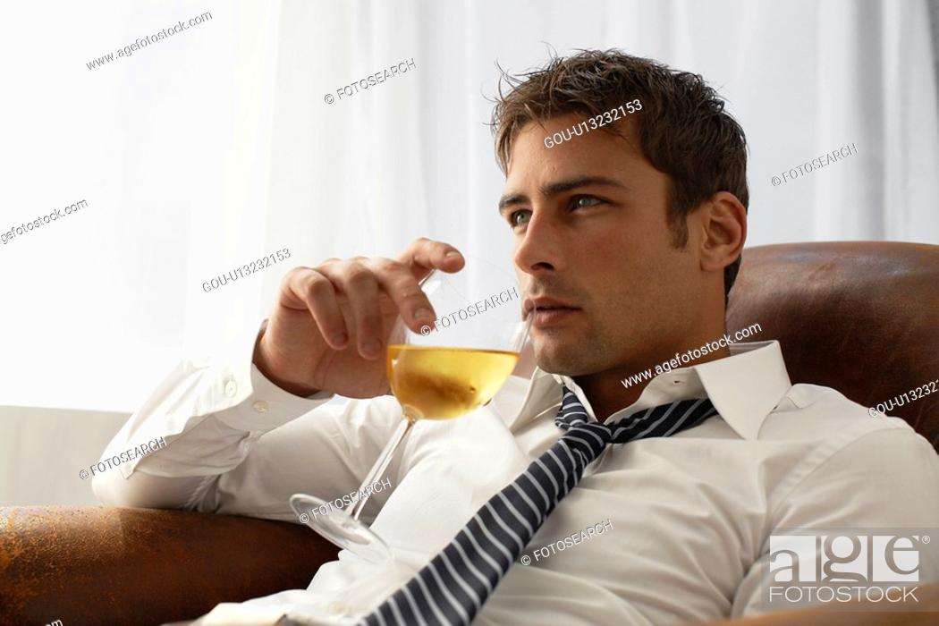 Stock Photo: Mid adult businessman drinking white wine on armchair.