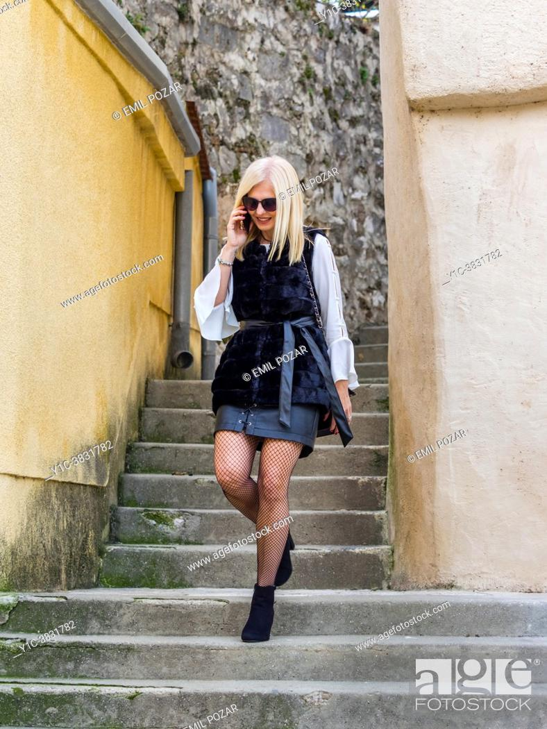 Stock Photo: Attractive mature blonde woman walking and talking using smartphone.