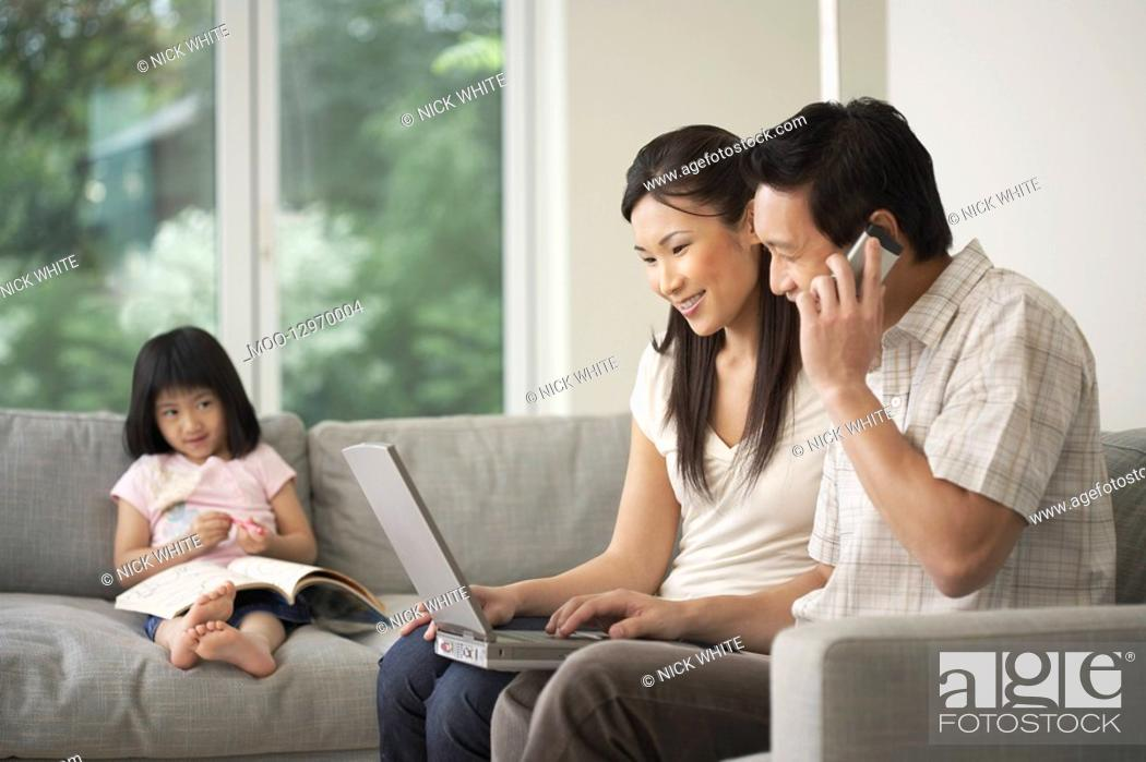 Stock Photo: Asian couple using laptop on sofa with daughter watching in background.
