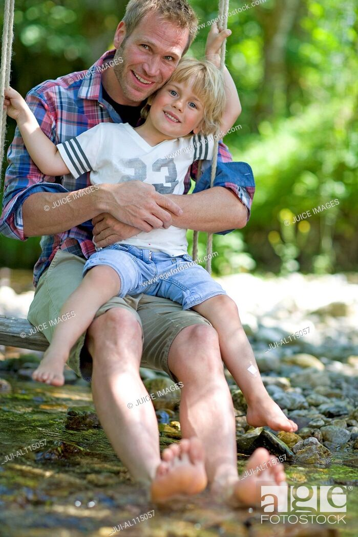 Stock Photo: Man and young boy on swing over river.