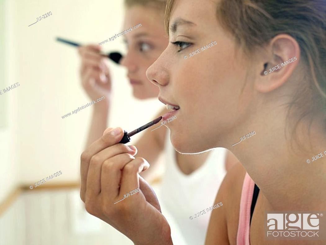 Stock Photo: Two teenage girls 15-17 applying make-up in bathroom, close-up, profile.
