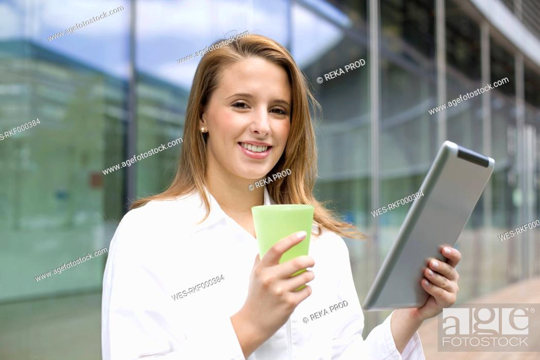 Stock Photo: Europe, Germany, North Rhine Westphalia, Duesseldorf, Medical student with digital tablet, smiling, portrait.