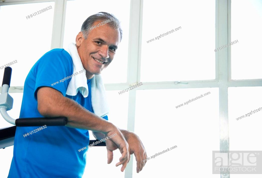 Stock Photo: Mature man on exercise machine (portrait).