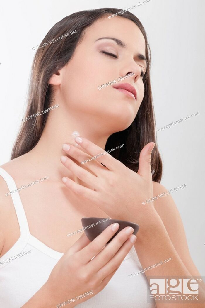 Imagen: Woman applying moisturizer cream on her neck.