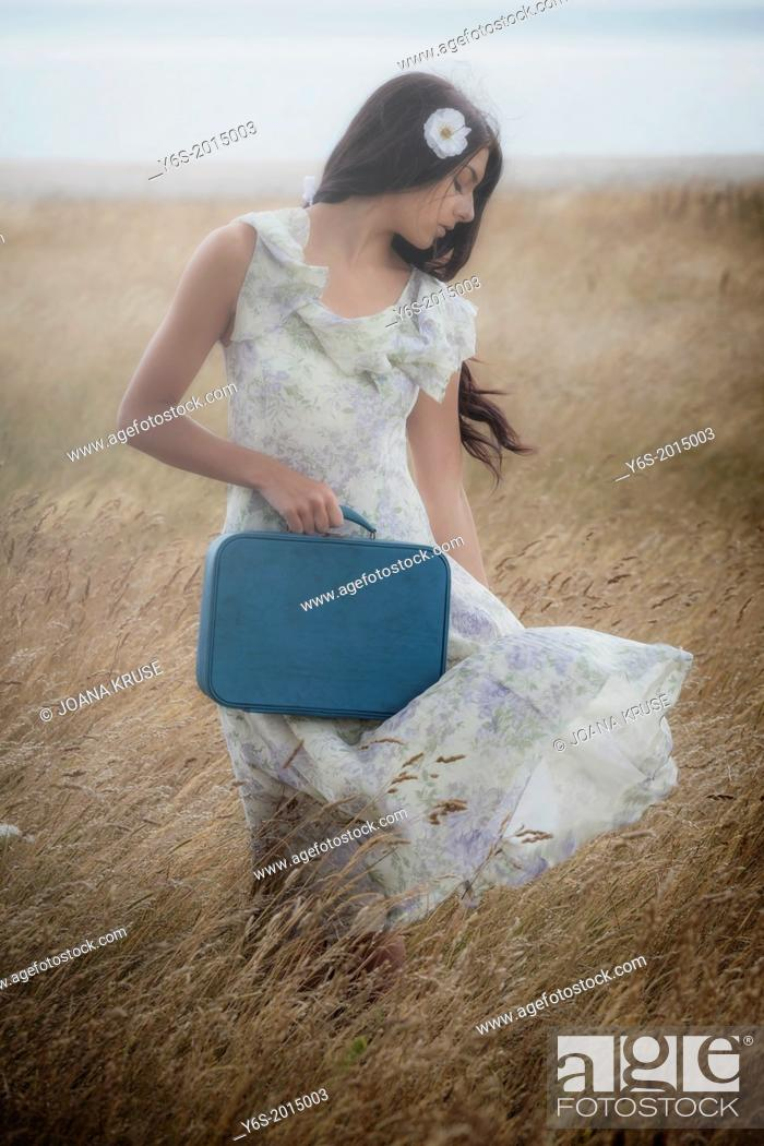 Stock Photo: a girl in a floral dress on a field with a suitcase.