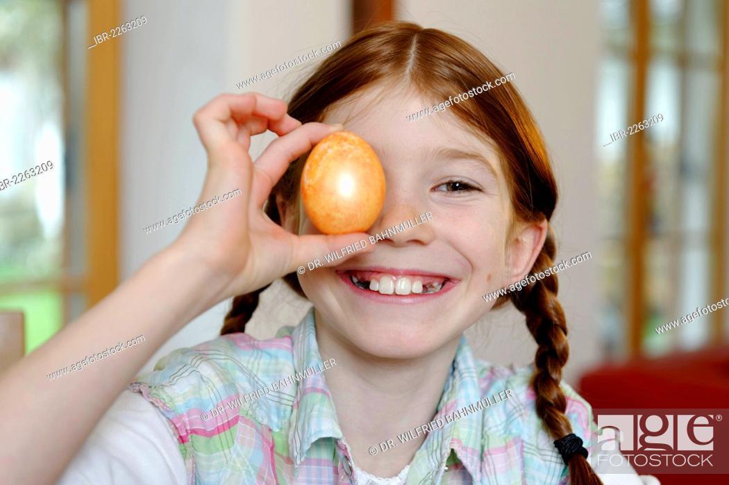 Stock Photo: Child, girl holding a coloured Easter egg.