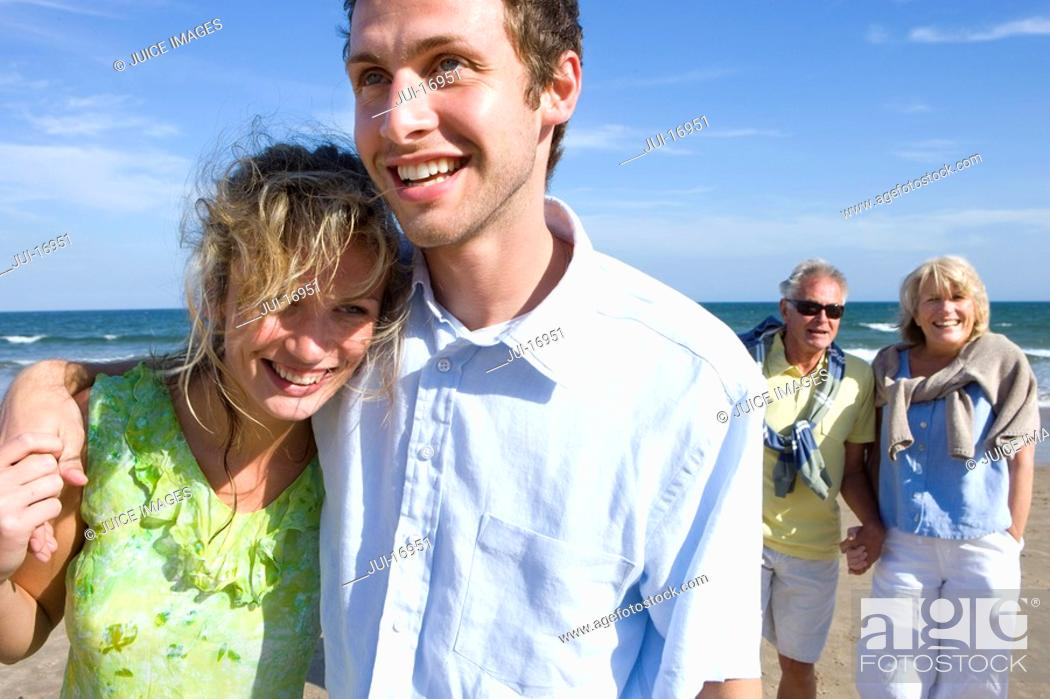 Stock Photo: Young couple walking on beach, senior couple in background.