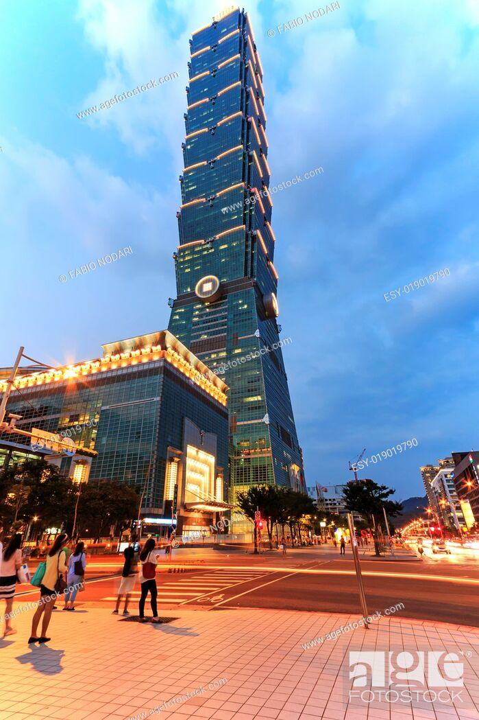 Stock Photo: Taipei, Taiwan: Taipei 101, one of the tallest skyscraper in the world, at twilight and tourists walking nearby.