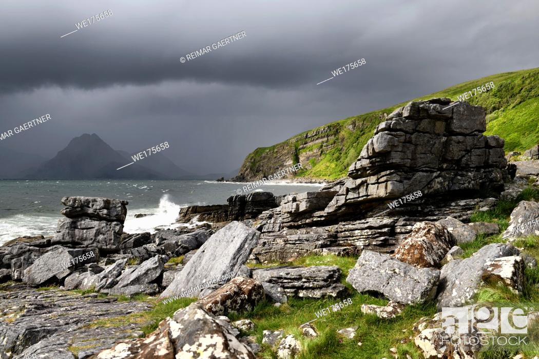 Stock Photo: Cliffs and shore north of Elgol Port na Cullaidh with Red Cuillin Mountains under dark clouds on Loch Scavaig Isle of Skye Scotland UK.