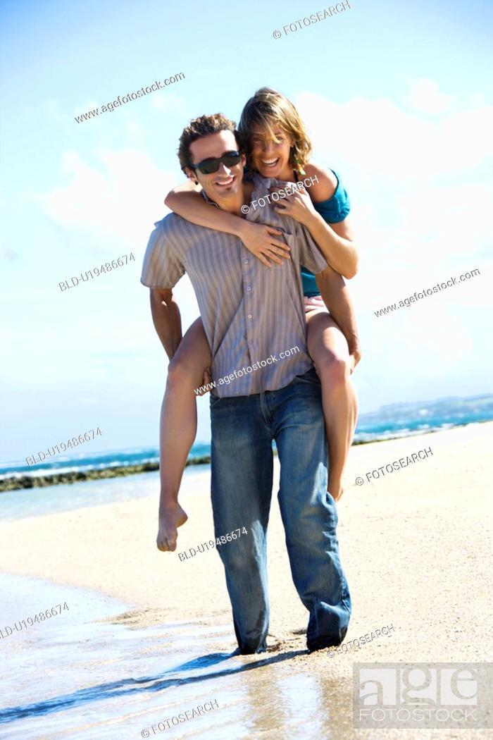 Stock Photo: Man giving woman piggyback ride on beach.