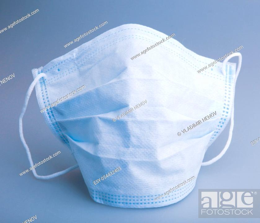 Stock Photo: Typical three-layer protective surgical mask. The edge with double stitches is designed to cover the nose, and a metal wire is concealed within so the mask can.