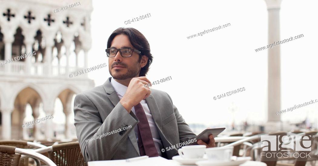 Stock Photo: Smiling businessman using digital tablet at sidewalk cafe.