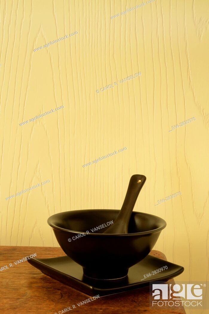 Stock Photo: Dark bowl, plate and spoon sitting on corner of wooden table.