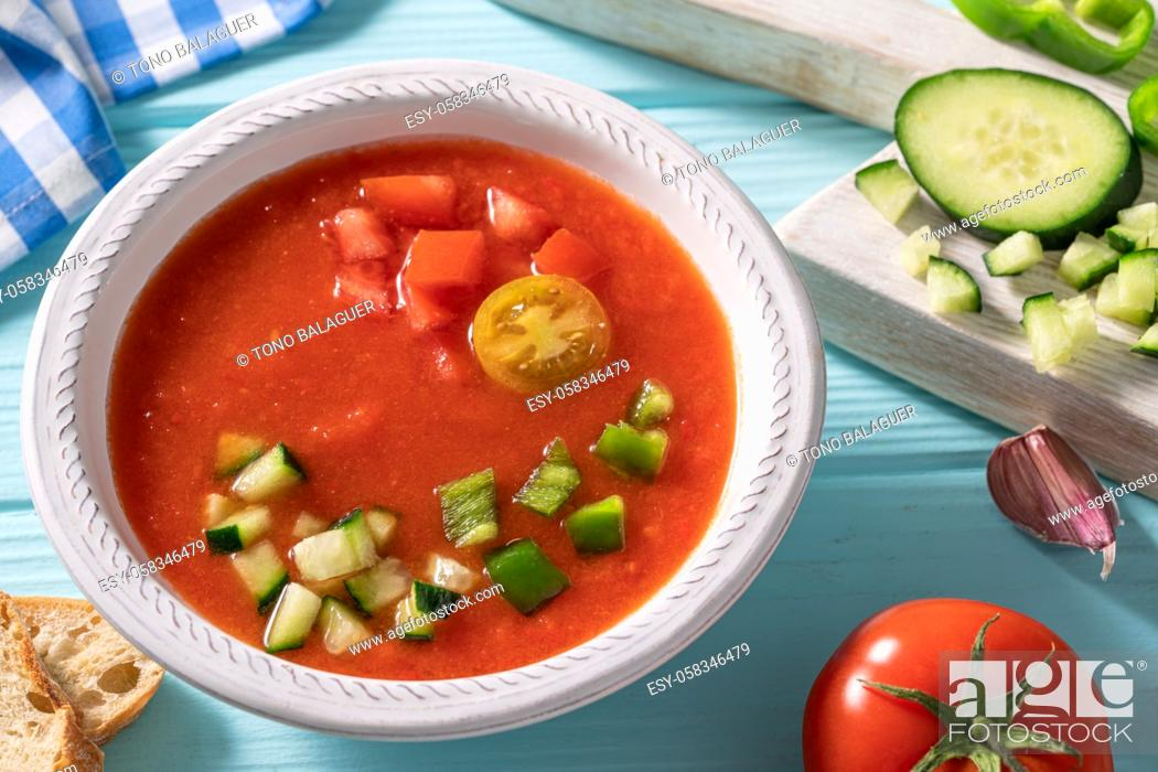 Photo de stock: Gazpacho Andaluz is an Andalusian tomato cold soup from Spain with cucumber, garlic, pepper on light blue background.