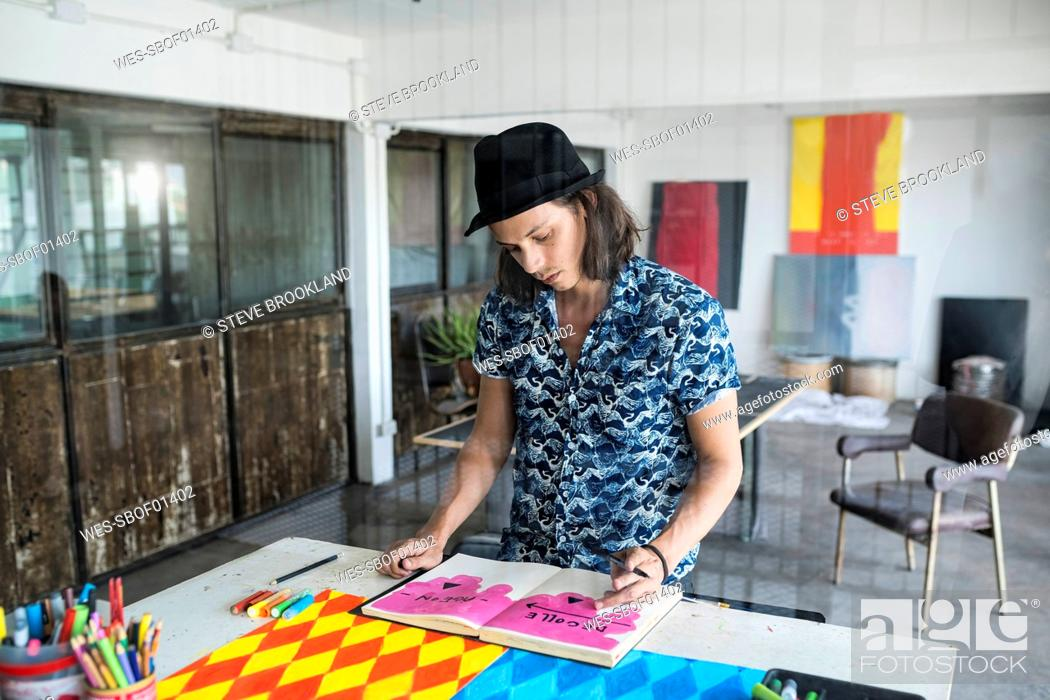 Stock Photo: Artist at work, drawing in a notebook in his loft studio with paintings and artwork in the background.