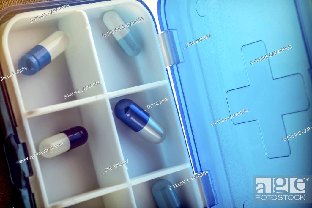 Photo de stock: Pillbox with capsules blue and white, conceptual image.