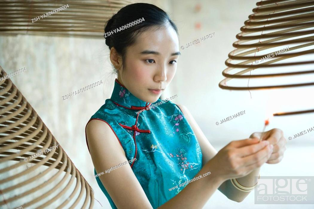 Stock Photo: Young woman dressed in traditional Chinese clothing lighting spiral incense.