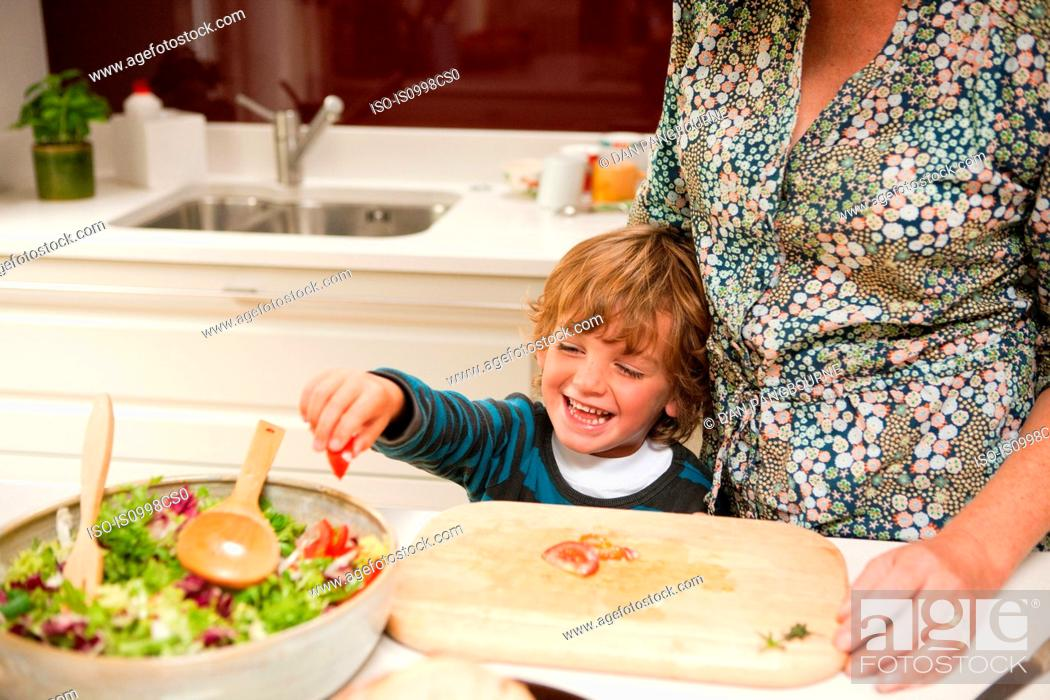 Stock Photo: Young boy helping mother to prepare salad together at home.