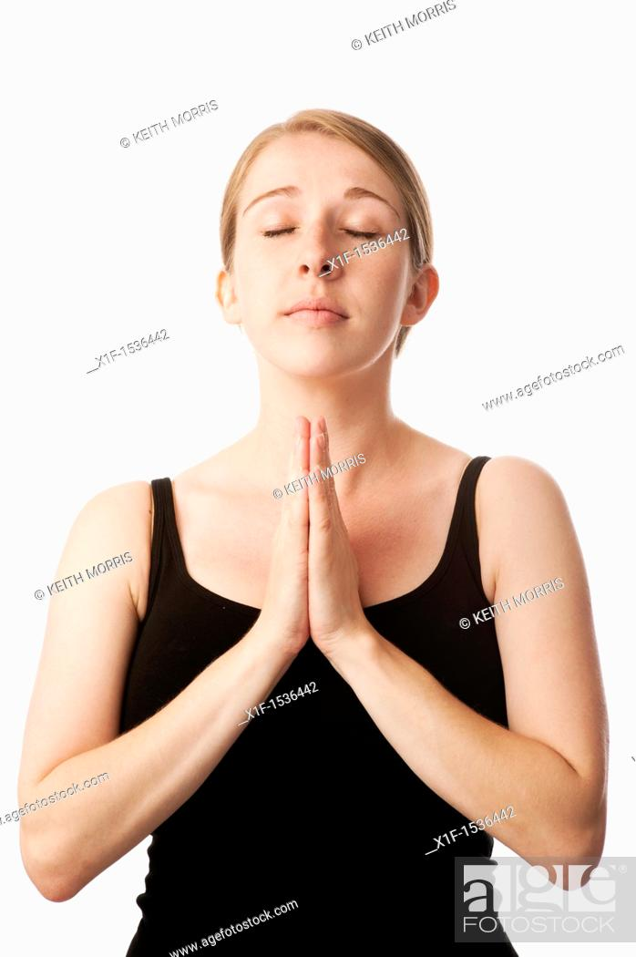 Stock Photo: a young caucasian woman looking angelic and praying with her hands together.