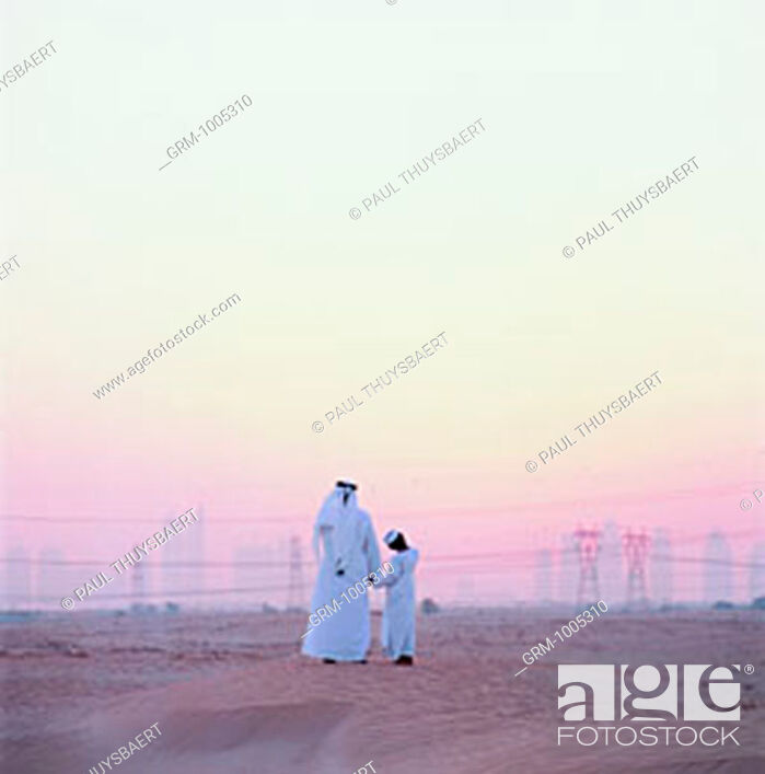 Stock Photo: Emirati father and son looking out to skyline of Dubai, UAE.