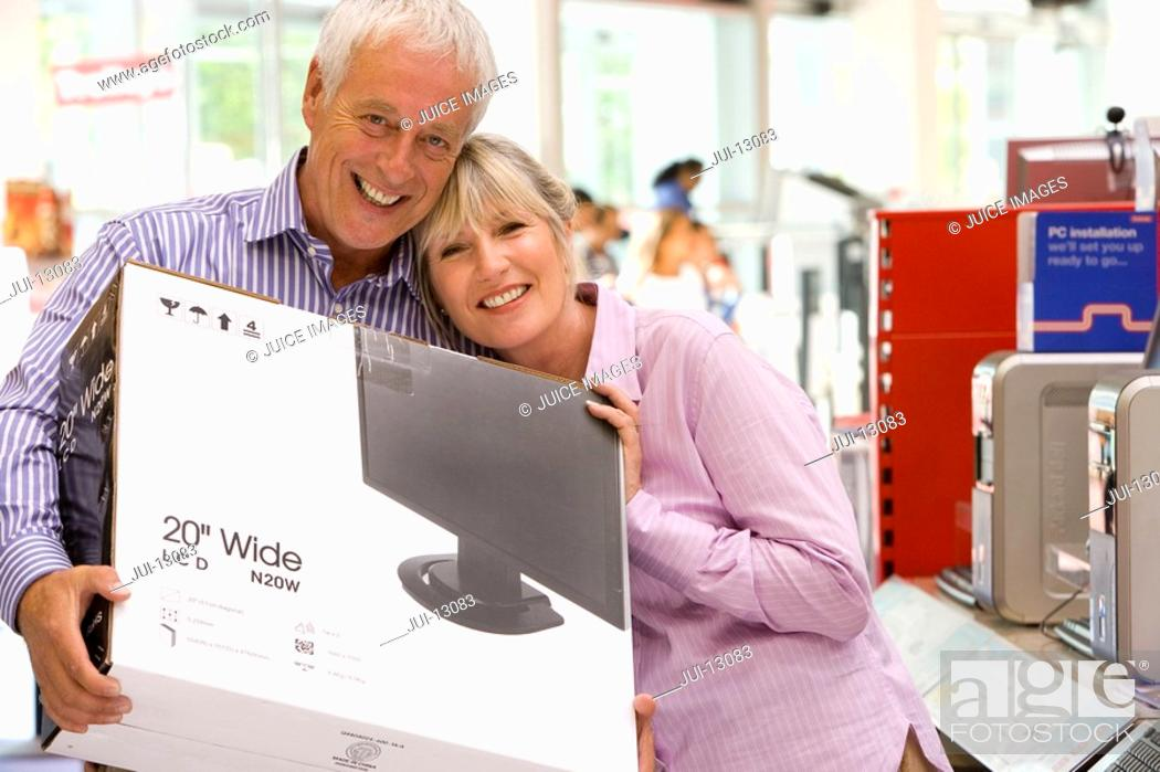 Stock Photo: Mature couple shopping, man with computer in box, smiling, portrait.