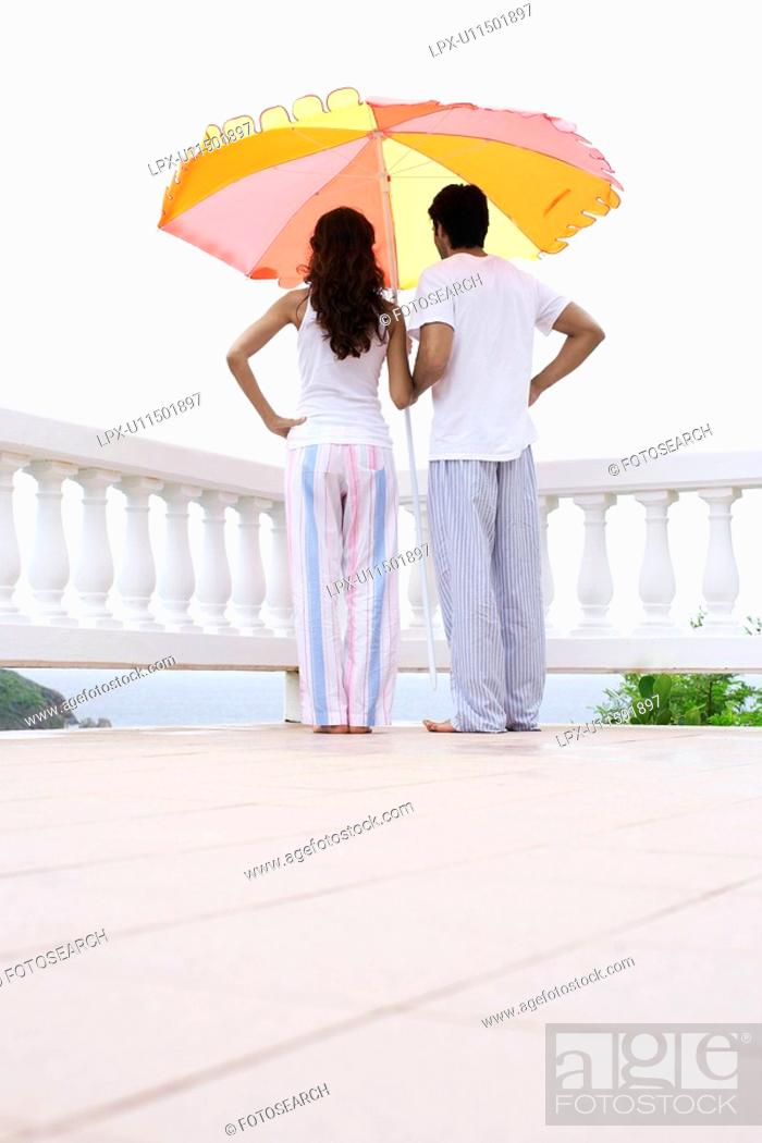 Stock Photo: Young couple standing under parasol and looking at view.