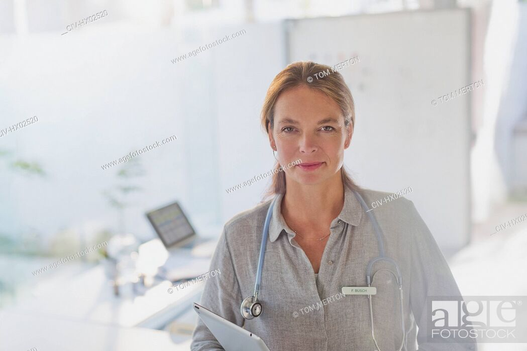 Stock Photo: Portrait confident female doctor with digital tablet in doctor's office.