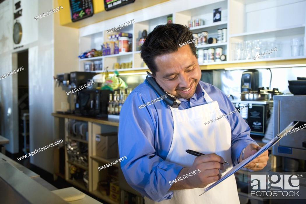 Stock Photo: Hispanic cafe owner placing telephone order.