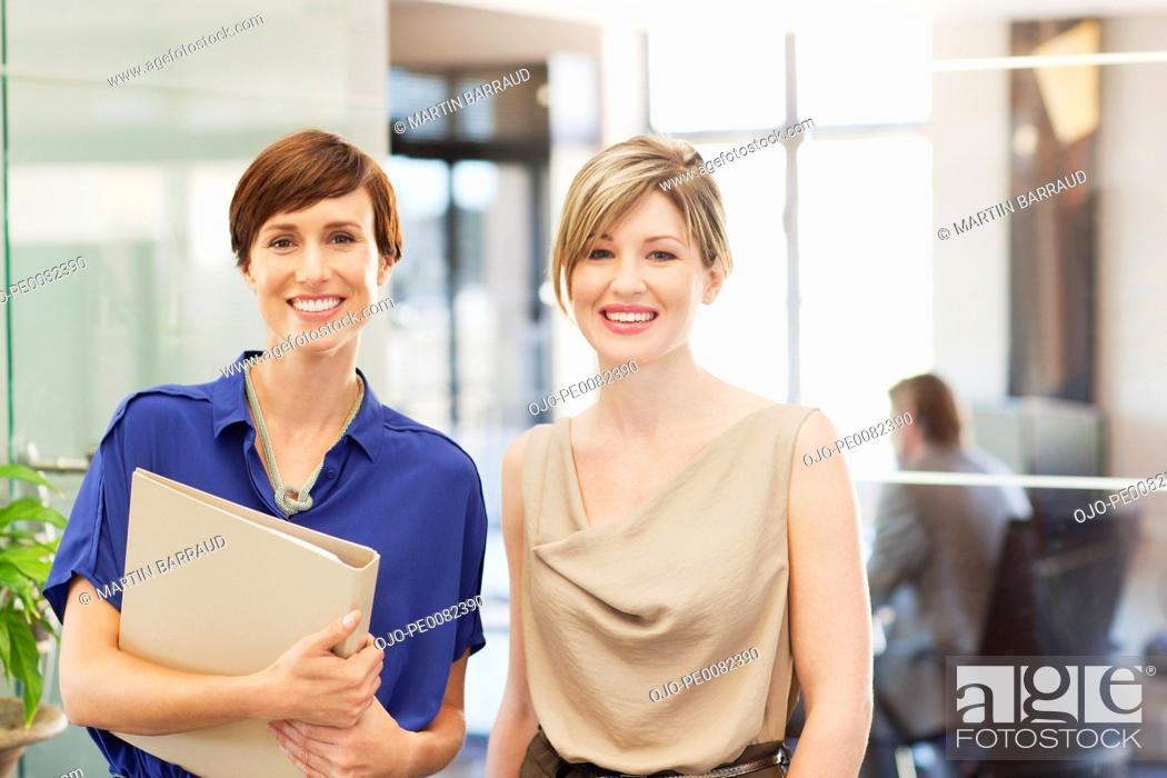 Stock Photo: Portrait of smiling businesswomen in office.