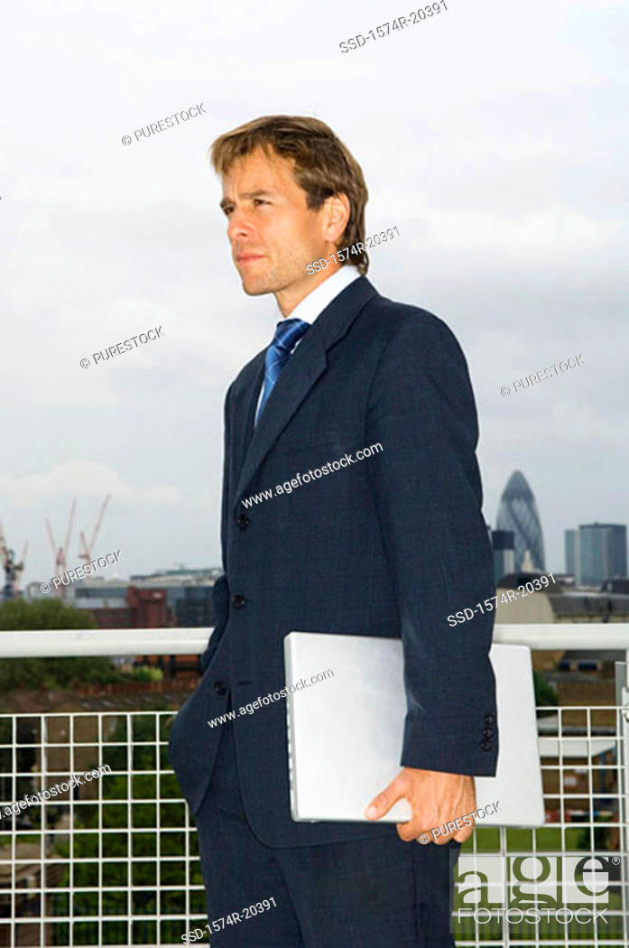 Stock Photo: Side profile of a businessman holding a laptop.