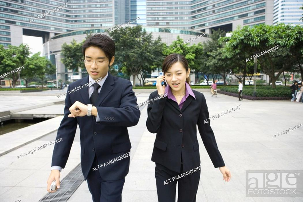 Stock Photo: Two young executives walking in office park, one checking watch while other uses cell phone.