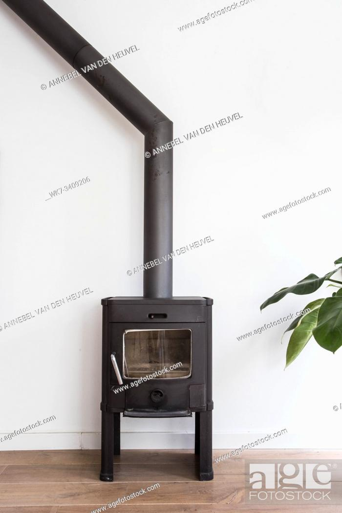 Stock Photo: iron fireplace like a stove in a house with fire, scandinavian interior modern design, white room empty.