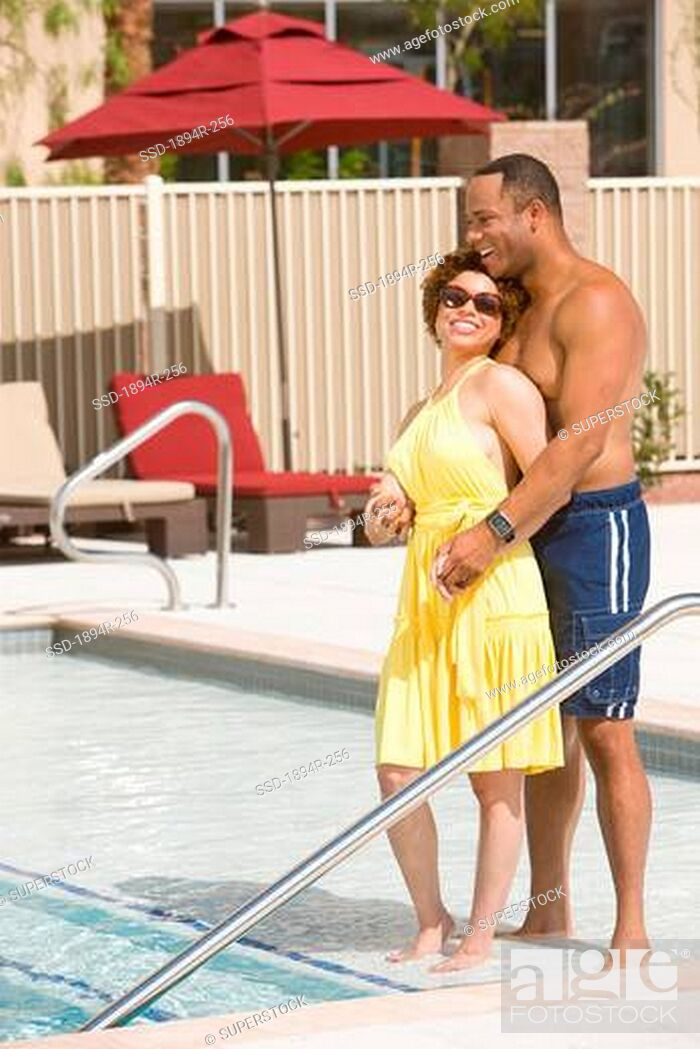 Imagen: Young couple romancing at the poolside.