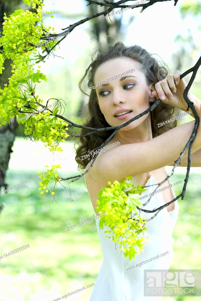 Stock Photo: Young woman holding flowering tree branch, looking away.