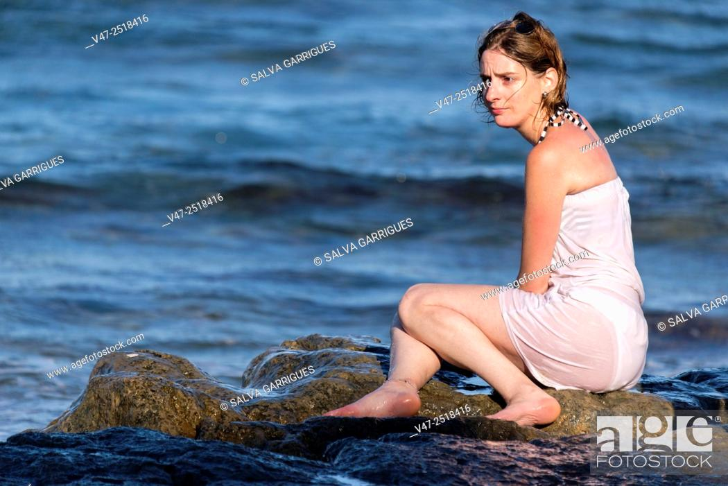 Imagen: Woman sitting on a rock in a cove of Javea, Spain, Europe.