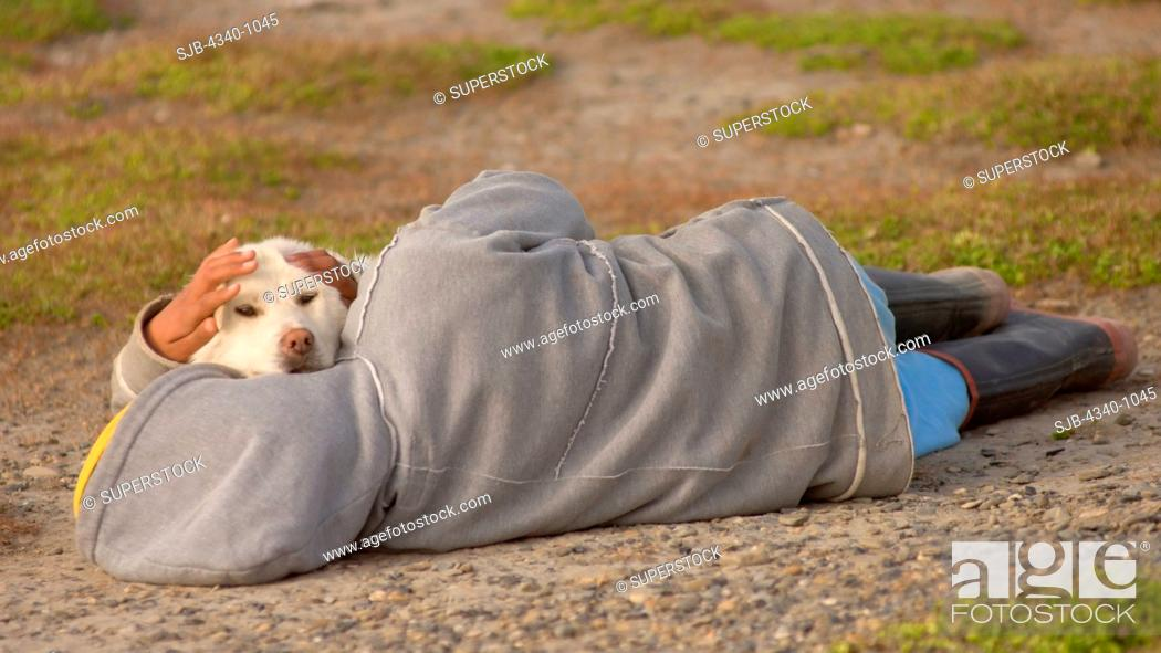Stock Photo: Young Inupiaq Girl Rests With Her Dog Along The Arctic Coast Of Alaska.