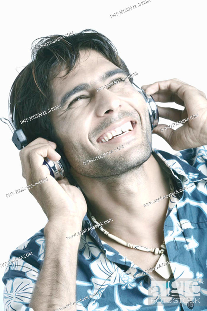 Stock Photo: Young man wearing headphones listening to music.