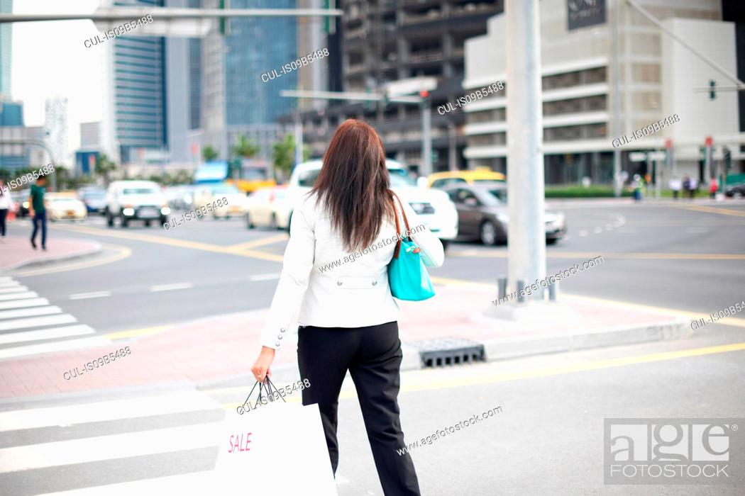 Stock Photo: Rear view of woman with shopping bags strolling along street, Dubai, United Arab Emirates.