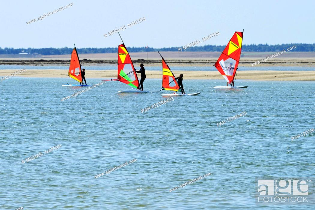Stock Photo: Four colourful windsurf sails on the blue water from the tide way Amrumtief with the island Amrum on the horizon in the background.