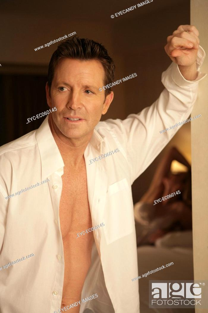 Stock Photo: Mature couple in bedroom, man leaning against doorway.