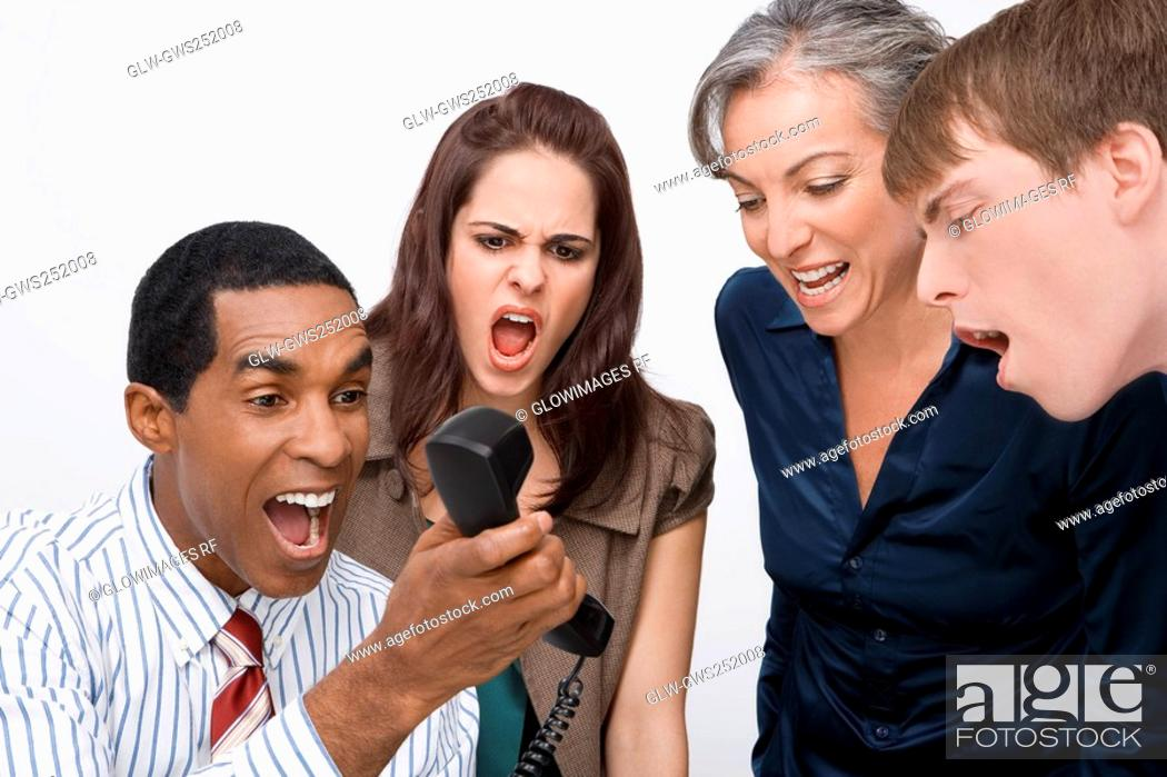 Stock Photo: Businessman holding a telephone with three business executives shouting.