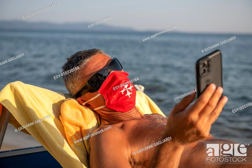 Photo de stock: Man wearing mask and reading smartphone on the beach in covid times.