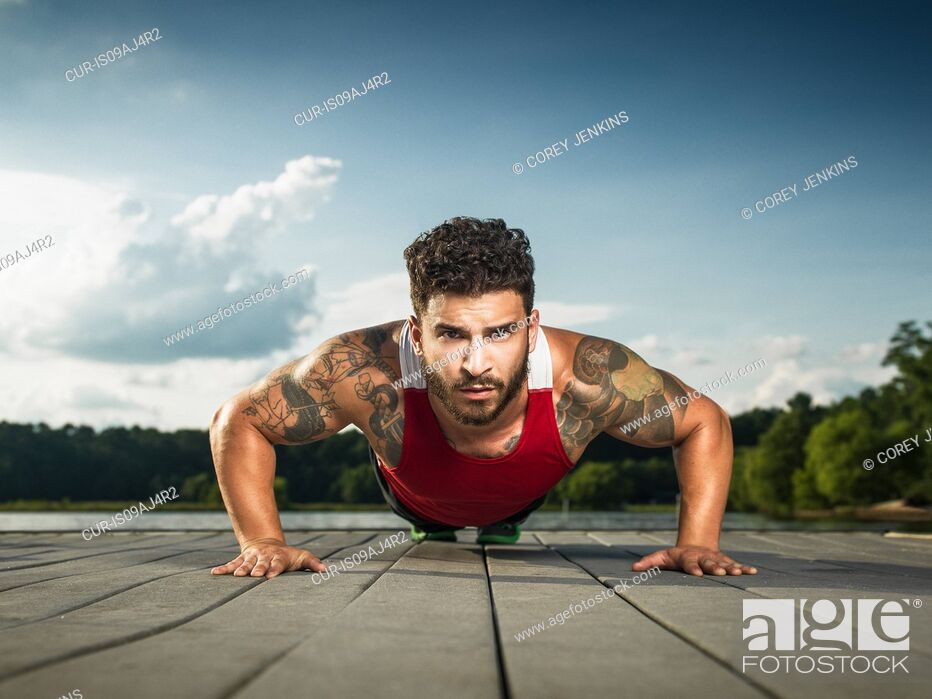 Imagen: Surface level portrait of young man doing push ups on lake pier.
