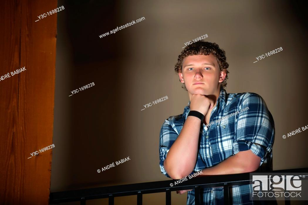 Stock Photo: Portrait of young man standing behind handrail.