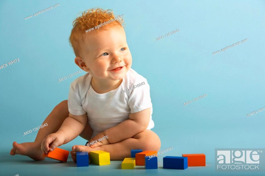 Stock Photo: Redheaded Baby Playing With Blocks.