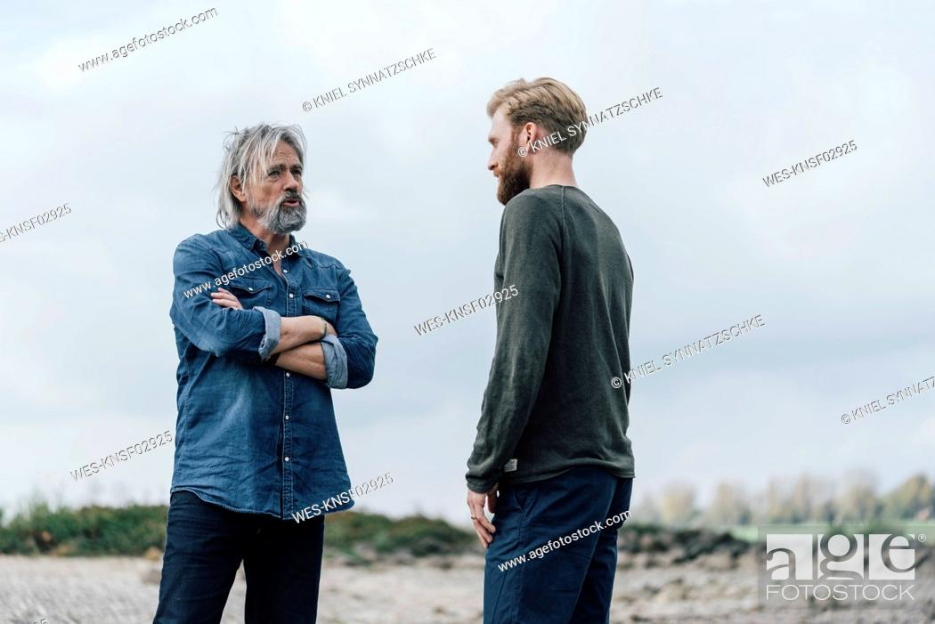 Stock Photo: Father and son meeting outdoors, talking together.
