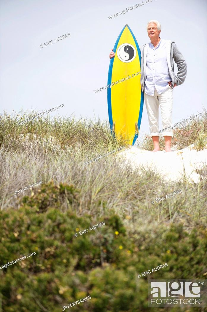 Stock Photo: Senior man standing with surfboard on the beach.