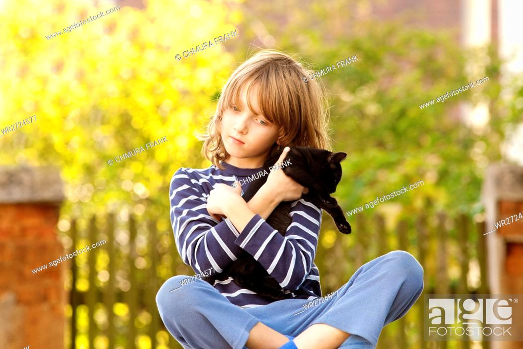Stock Photo: Boy Sitting Holding a Pet Kitten.