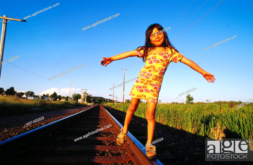 Stock Photo: Girl, 6 years old, balancing on railroad track.